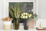 Kitchen utensils, roses, and plants are sorted in front of a window.