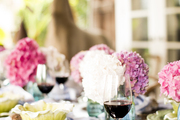 A brown outdoor table with hydrangea and red wine