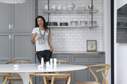 Designer and homeowner Susan Greenleaf in her San Francisco kitchen, with gray custom cabinetry, open shelving, white subway tile, a Saarinen table, and Hans Wegner Wishbone Chairs