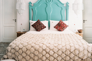 A bright blue headboard in a neutral bedroom