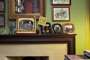Wooden fireplace mantel covered in photos.