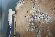 A detailed view of a distressed antique highchair