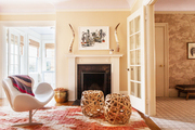 A pair of bentwood ottomans and a midcentury-inspired chair in a sitting area
