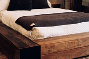A low wooden bed with white and gray bedding atop a patterned rug