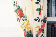 Floral curtains with beaded tie-backs beside a white bookcase