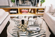 A glass coffee table atop a zebra-print rug in a neutral living space