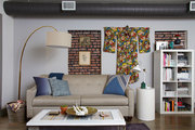 A large gold lamp and hanging kimono frame a beige sofa