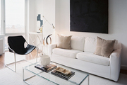 A white couch paired with a minimalist black chair
