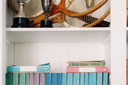 Trophies, rackets, and books in a white bookcase