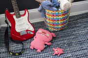 A boy's room with a blue rug, a toy guitar, and stuffed animals in a basket