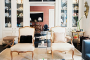 A pair of chairs in front of white built-in china cabinets