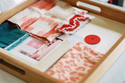 A wooden tray of fabric samples and inspirational images