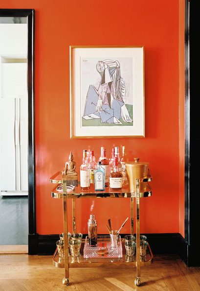 Bar Cart - A brass bar cart below framed art