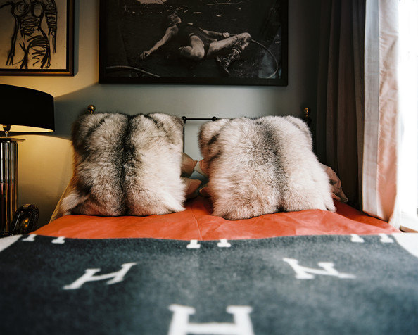 Bedroom - Fur throw pillows and orange bedding topped with a gray blanket in a bedroom