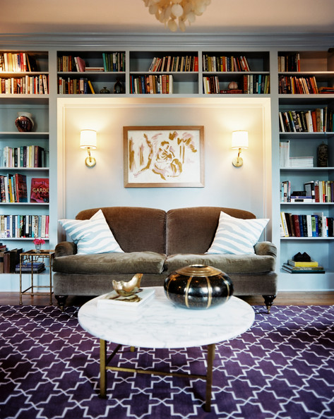 Blue Bookshelf - Built-in bookcases surrounding a brown couch and a pair of wall sconces