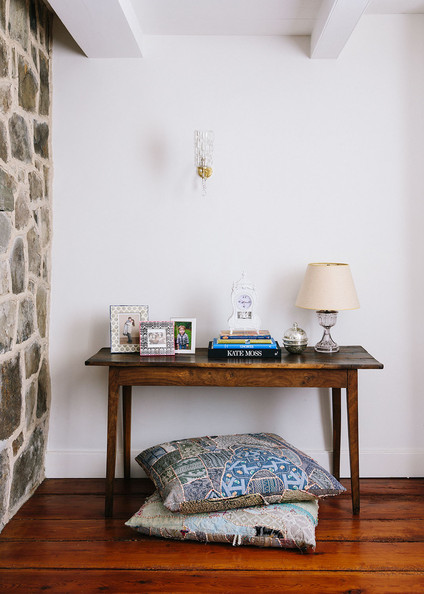 Books - Patterned floor pillows beneath an antique console table