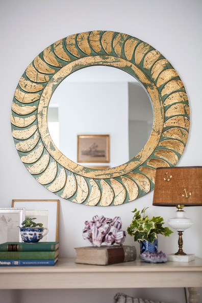 Books - A round gold mirror above a console table