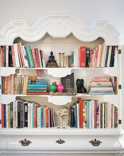 Bookshelf - A white cabinet filled with books and decorative objects