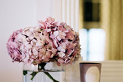 A vase of pink flowers atop a white mantel