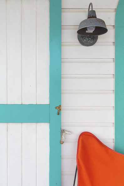 Butterfly Chair - A rustic tin sconce against pastel-trimmed clapboard siding
