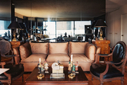 A pair of black leather chairs and a camel-colored couch surrounding a wooden coffee table