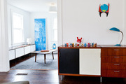 Wall art above a console topped by a table lamp and colorful objets