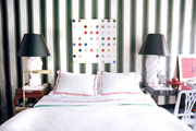 White bedding flanked by a pair of white lamps with black shades