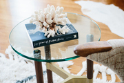 Coral decor and book atop a small glass coffee table.