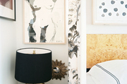 A grouping of art above a black bedside table