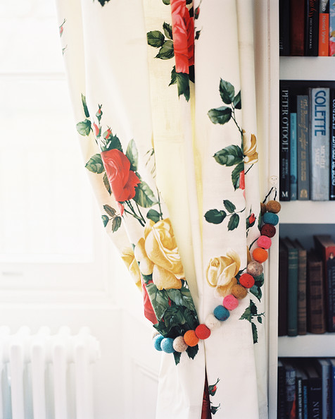 Cath Kidston - Floral curtains with beaded tie-backs beside a white bookcase