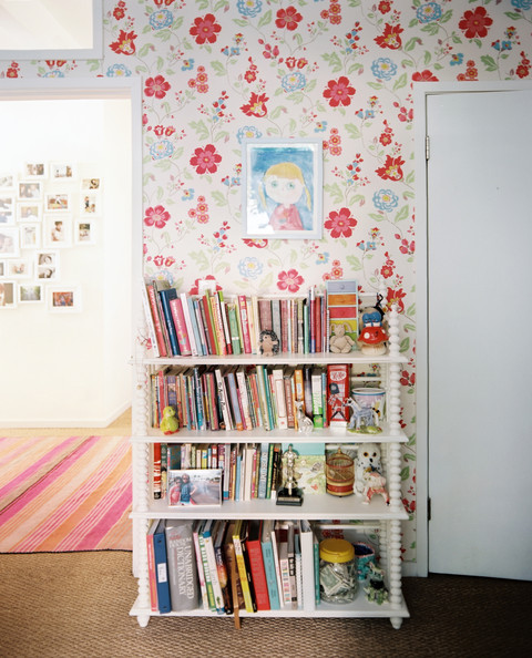 Cath Kidston - A bookshelf against floral-patterned wallpaper and a sisal rug