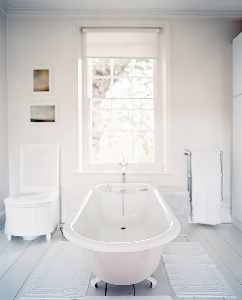 Cath Kidston - A freestanding claw-foot tub in a white bathroom