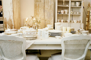 White cane-back chairs surrounding a white dining table covered with china