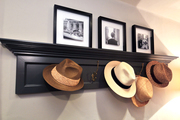 Three black and white photos sit atop a black coat hanger holding hats.