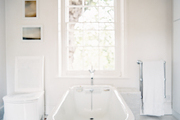 A freestanding claw-foot tub in a white bathroom