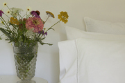 White bedding contrasted against colorful flowers on a white nightstand.