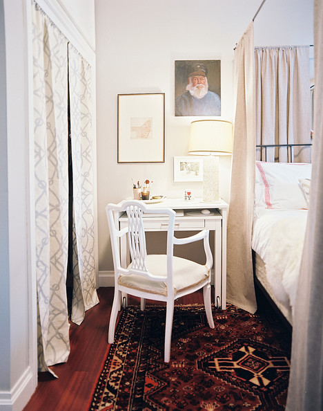 Closet Curtains - A four-poster bed and a patterned rug in a bedroom with white walls