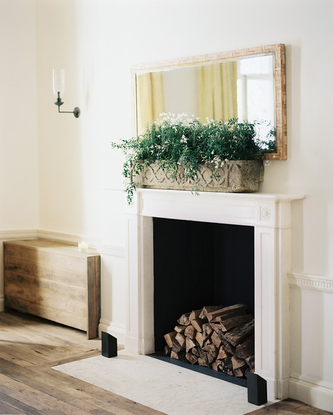 Colonial Fireplace - A white mantel topped with a rectangular mirror and a planter
