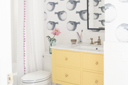 A small contemporary bathroom with black and white wallpaper and colorful accents.