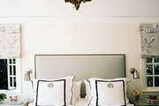 Roman shades flanking an upholstered bed with monogrammed bedding