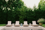 A grouping of wicker chaises beside a pool