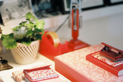A grouping of red desk accessories beside a potted plant