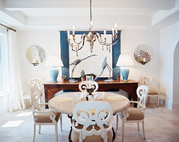 Dining Room - White chairs, a round wooden table, and a pair of mirrored sconces in a dining space