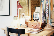 A rustic wood desk with a red task lamp