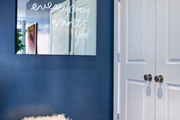 A blue accent wall with a furry pouf and a mirror.