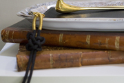 A gold bird letter opener sits atop leather bound journals