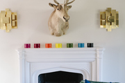This mantle is topped with colorful accents and a deer head with a comfy seat nearby.