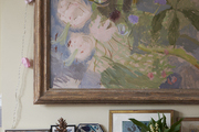 An abstract floral painting sits above a fireplace with eclectic personal touches.