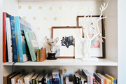 A white bookshelf backed with polka-dot paper