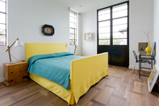 Yellow bed with blue bedding and wood nightstand.